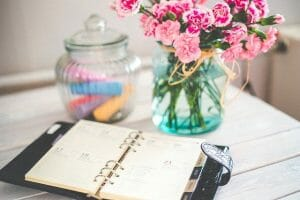planner and vases on a white wood desk