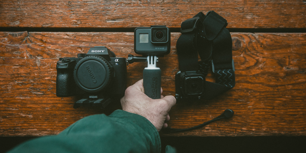 a man's hand holding a mini camera