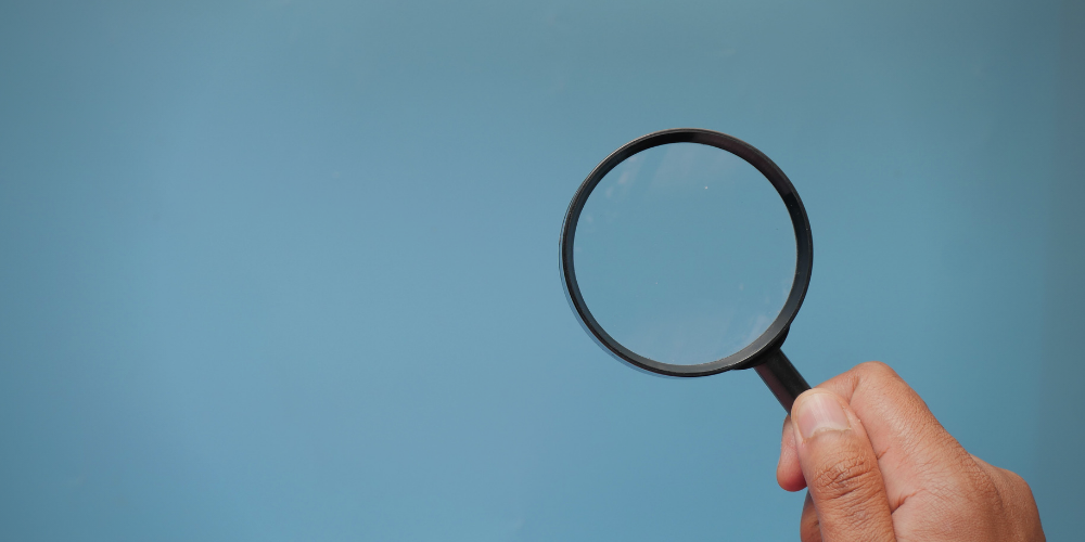 a man's hand holding a magnifying glass