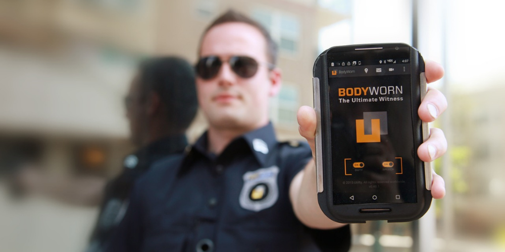 a male police officer showing his body camera