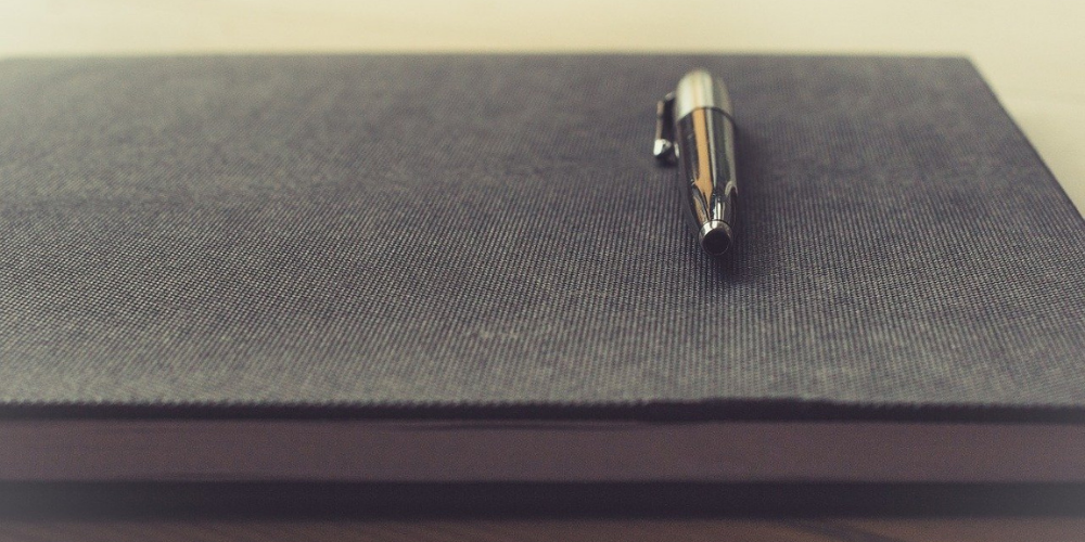 a pen at the top of a black notebook