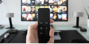 a man's hand holding a remote in front of a TV set