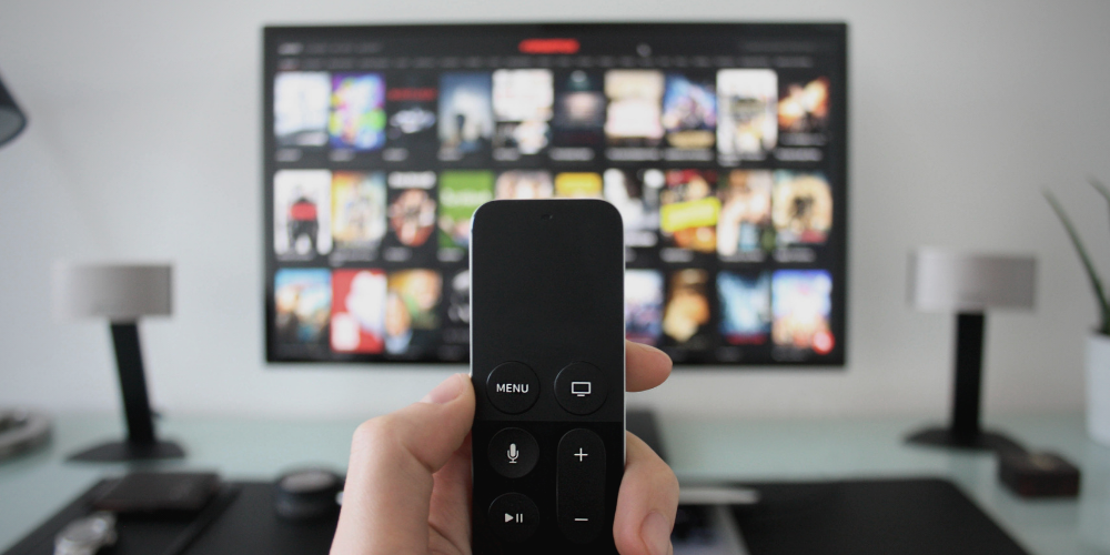 a man's hand holding a remote control in front of the TV